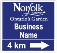Purple sign for businesses in Norfolk County - Ontario's Garden. 4km with arrow pointing to the right.
