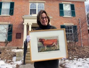 Roberta Grosland stands with a piece from the upcoming Branding, Butter and Bulls exhibit curated by Samantha Purvis-Johnston, which showcases the agricultural art of farming legend Ross Butler